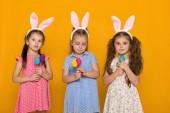 kislányok a húsvéti nyuszi füle gazdaság színes tojás