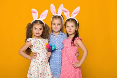 Three little girls with Easter bunny ears holding colorful eggs on yellow background. Happy easter. cute children stock vector