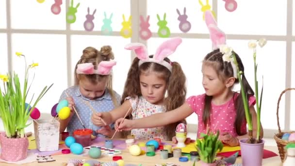 Happy children wearing bunny ears painting eggs on Easter day.