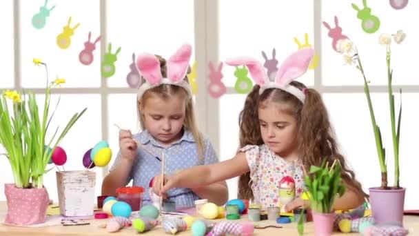 Boldog gyermekek visel nyuszi füle festés tojások, húsvét napján.