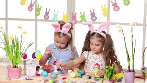 Šťastné děti na velikonočních uších malováním vajec na velikonoční den.