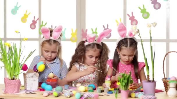 Glückliche Kinder mit Hasenohren beim Bemalen von Ostereiern.