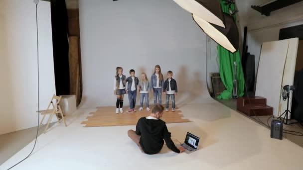 Fotografo che cattura le immagini di bambini felici in posa in studio fotografico.