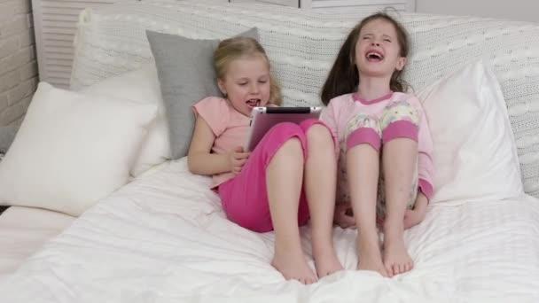 aranyos kis gyermek lány fekszik az ágyban használ digitális tabletta.