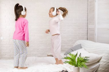 little children girls listening to the music with the headphones and dancing on bed.