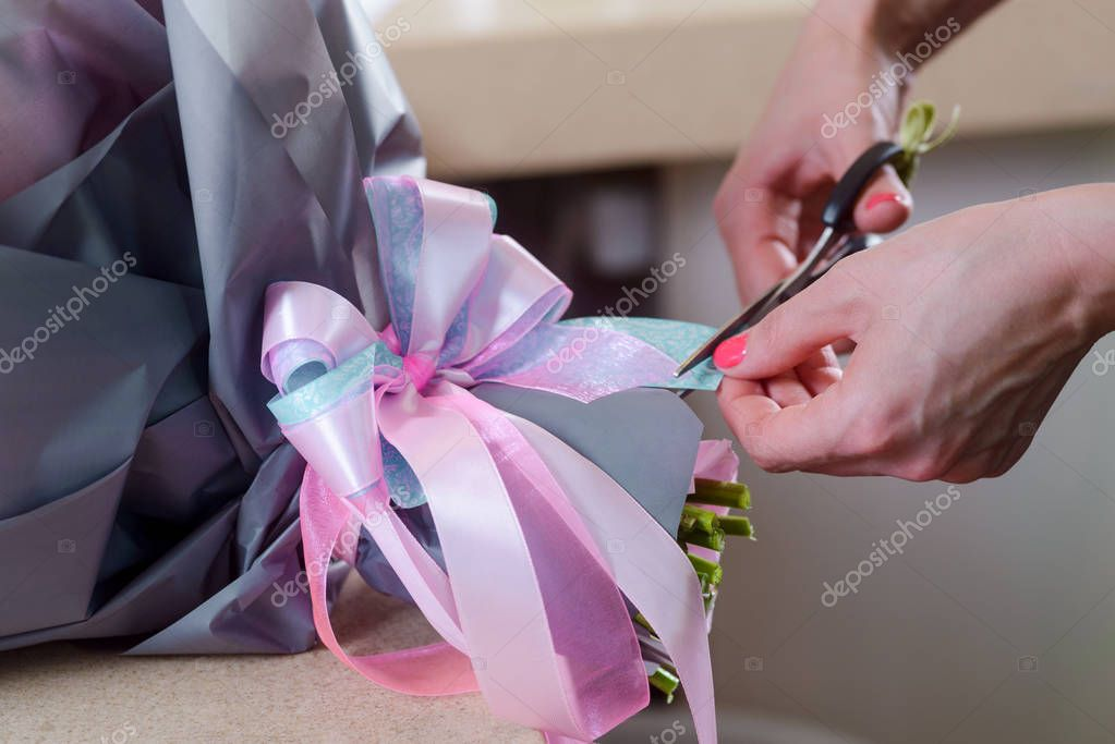 Florist creating design of bouquet. A bunch of flowers is beautifully decorated with gray wrapping paper and bow-knot made of blue and pink ribbons.