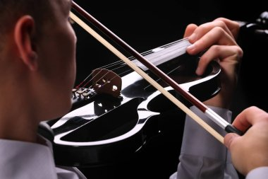 Young men playing the violin with black background