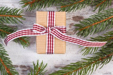 Wrapped gift tied colorful ribbon for Christmas or other celebration and green spruce branches