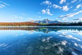 Fotografie Wide angle view of Patricia Lake with Pyramid Mountain in the background and misty fog on the waters surface. Calm waters create serene reflections.