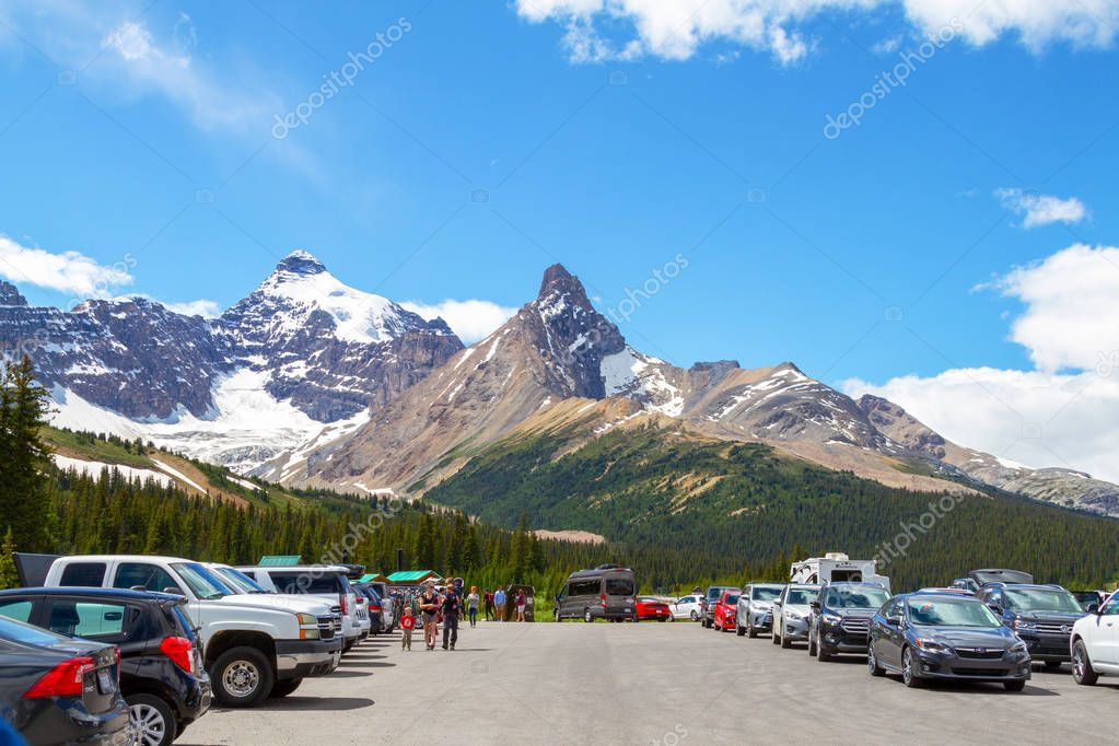 JASPER, CANADA - JUL 8, 2018: Visitors stop at the Parker Ridge hiking trailhead parking lot on the Icefields Parkway in Jasper National Park with Hilda Peak and snow-covered Mt Athabasca in the background.