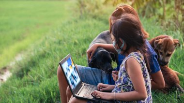 Happy two little child girl learning outdoor by studying online and working on laptop in green field with wearing face mask