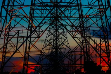 electric power concept : high voltage tower and electric pole with twilight sky on background