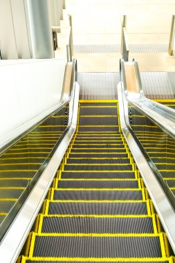 Escalator in train station, Shopping Center or Department Store. Moving Staircase. Neon Light, Modern Escalator