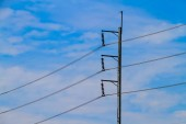 Fotografie electric pole with electric cable on the blue sky background