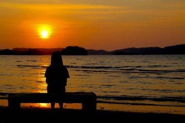 Alone concept :Alone girl sitting near the sea