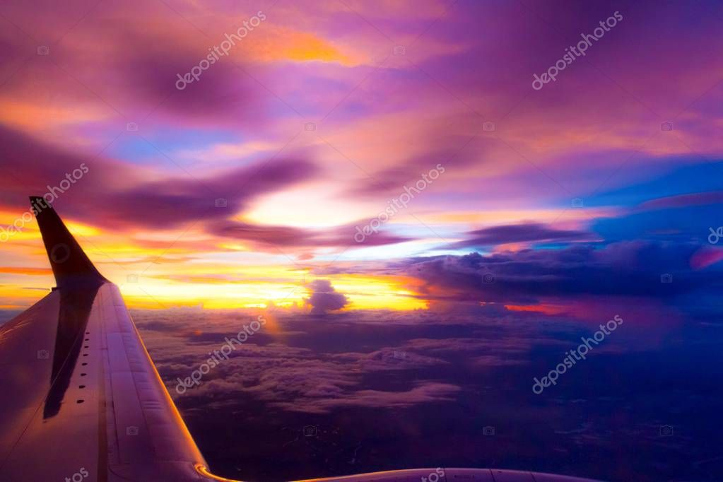 blurry of Twilight and sunset over the clouds and the wing of the plane.