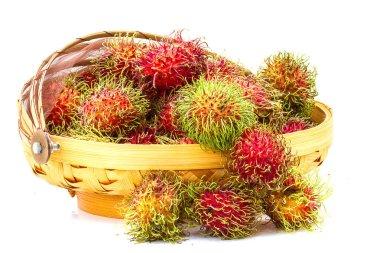 Fruit basket of rambutan on a white table.