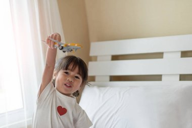 Happy Asian child enjoy playing with toy airplane in hands