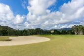 golfové hřiště v Nové Kaledonii s modrou oblohou. Hills in the background