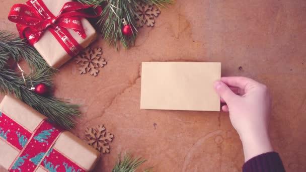 Boldog karácsonyi concept fenyő fa ágai, díszdobozok és kéz táblázat üres kártya felhelyezése