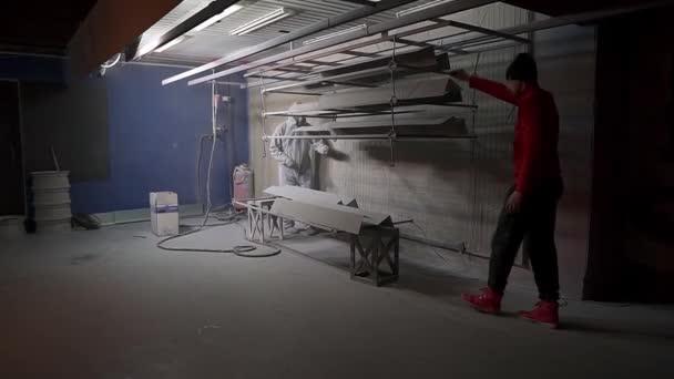 Ein Mann in roter Kleidung schiebt Metallprodukte in die Pulverbeschichtungskammer