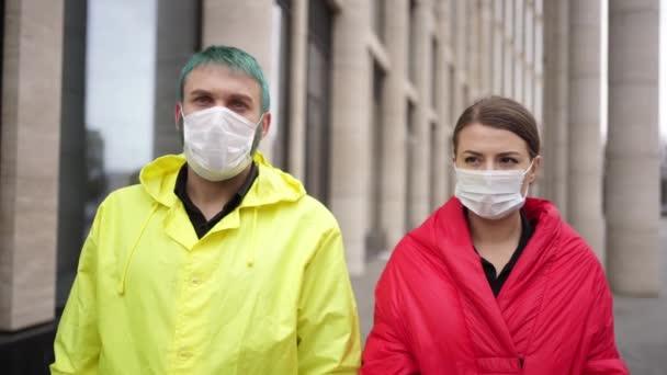 férfi és nő távolítsa el a védőmaszkokat az utcán
