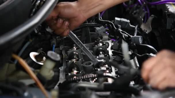 Car mechanic or serviceman checking a car engine (Valve Adjustment) for fix and repair problem at car garage or repair shop