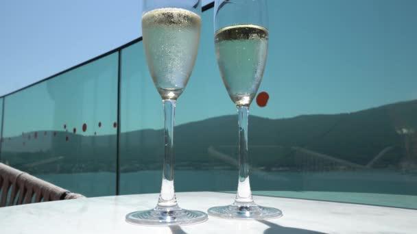 4K-Video Zwei große Sektgläser mit Blasen auf einem weißen Tisch gegen ein blaues, festliches Getränk mit Spiegelung.