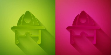 Paper cut Firefighter helmet or fireman hat icon isolated on green and pink background. Paper art style. Vector. icon