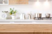 Dřevěný stůl na rozmazané kuchyňské lince pozadí pro zobrazení výrobku
