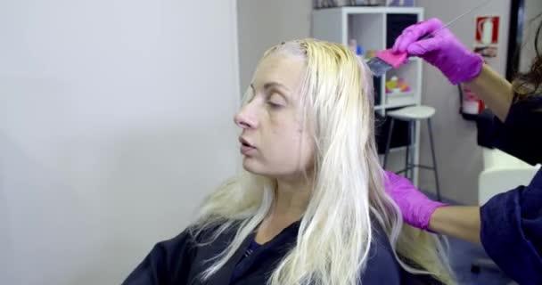 gyönyörű lány festi a haját, női fodrász