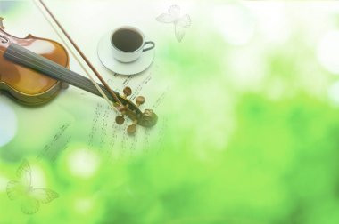 coffee cup and violin on green bokeh background
