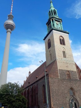 The Fernsehturm or telecommunications tower in the Alexanderplatz area of Berlin in Germany is close to the medieval Marienkirche church
