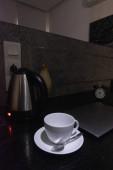 kávécsésze és elektromos vízforraló az asztalon
