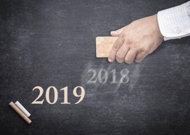 Happy new year concept: People hand holding eraser for change word