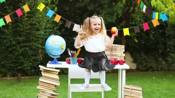 szőke lány diák egy iskolai egyenruhában az iskola asztalán integetett és nevetett
