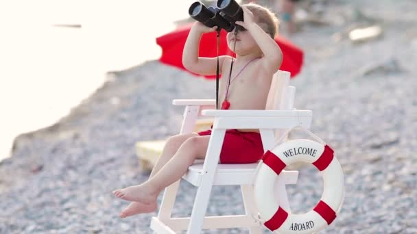 Cute boy sits on the lifeguards tower and looks through binoculars