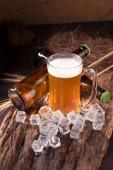 Fényképek Csapolt sör üvegedénybe, fából készült háttér