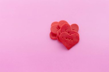 Red heart shaped sugar on pink background.