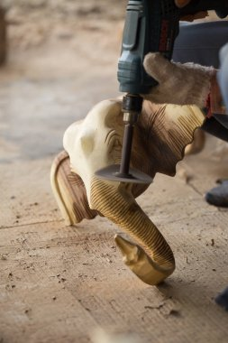 Traditional craftsman carving wooden elephant and sanding wood with motor sandpaper.