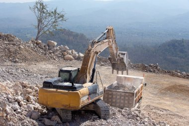 Yellow excavator is filling a dump truck with rocks at coal mine