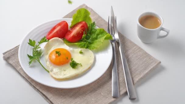 Egészséges és kiadós reggeli. Sült tojás, paradicsom, gyógynövények és eszpresszó kávé. Fehér asztalon tálalva, vászonszalvétával és evőeszközökkel..