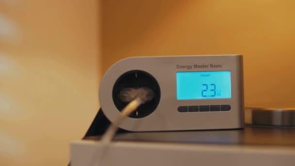 Detailní pohyblivý záběr zařízení na příborníku, který zamíchá spotřebu energie, když se rozsvítí světlo. Nízká spotřeba energie LED inteligentní domácí lampy, zatímco lampa se mění z teplé na studené.