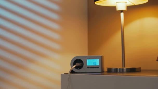 Pohybující se záběr zařízení na příborníku, který zamotává spotřebu energie, když se rozsvítí světlo. Nízká spotřeba energie LED inteligentní domácí lampy, zatímco lampa se mění z teplé na studené.