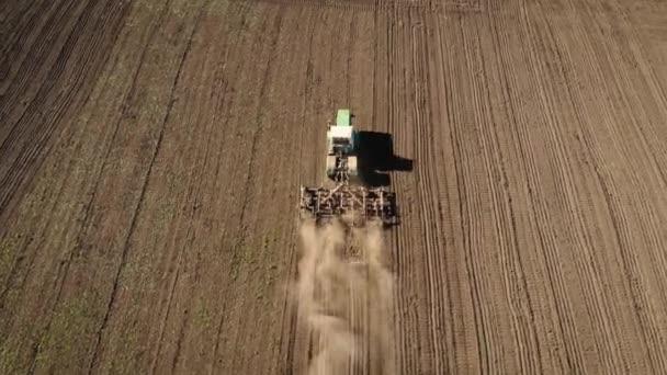 Nagy erős traktor szántás mezőgazdasági területen a por és előkészíti a földet a vetés