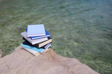 Stack of books on the beach by the sea