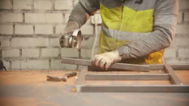 Muž dělník řezání kus kovového nosníku pomocí brusky stroje