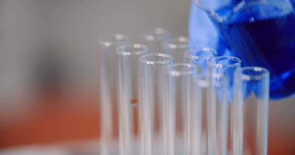 Wissenschaftler schüttet Flüssigkeit ins Reagenzglas