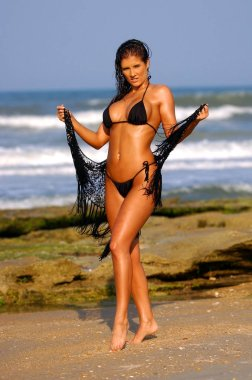 Healthy Athletic Brunette in Skimpy Outfit Posing Beach Side Playing in the sand near the rock and Ocean on Daytona Beach - Plenty of background and copy space and cleavage - Portrait layout  Active look - Black String Bikini with rap