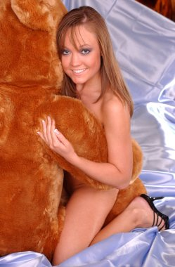 Beautiful young lady in implied nude pose huge tan teddy bear bare hugs hugging charming smile clear soft tan skin tones fun playful pose of love and alluring sensual tone butt cheeks backside rear end behind view of curved buttocks bottom boudoir